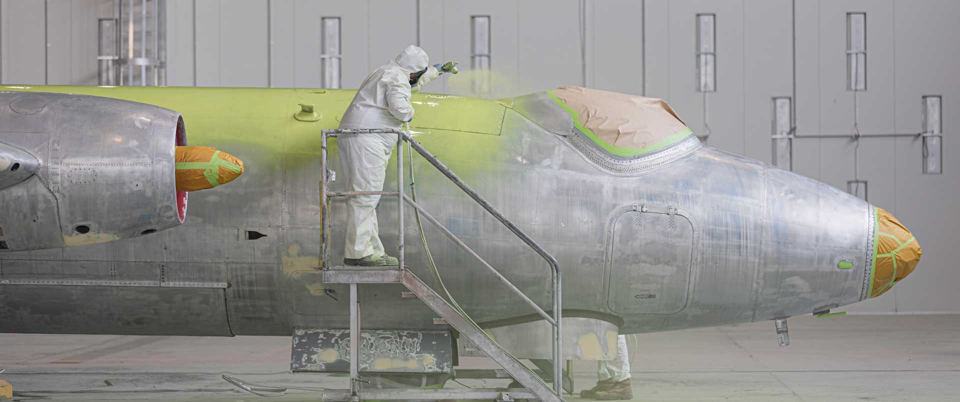 Two aircraft spray painters painting a fixed wing jet